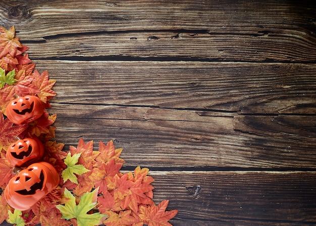 木製の上に秋の秋の葉を持つハロウィーンのカボチャ