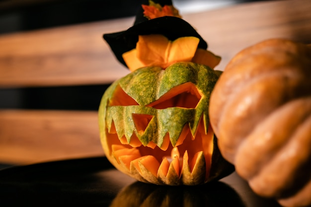 Halloween pumpkins with black witch hat on its, wooden