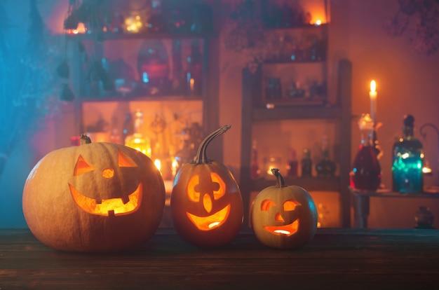 Тыквы на хэллоуин со свечами и волшебными зельями ночью в помещении