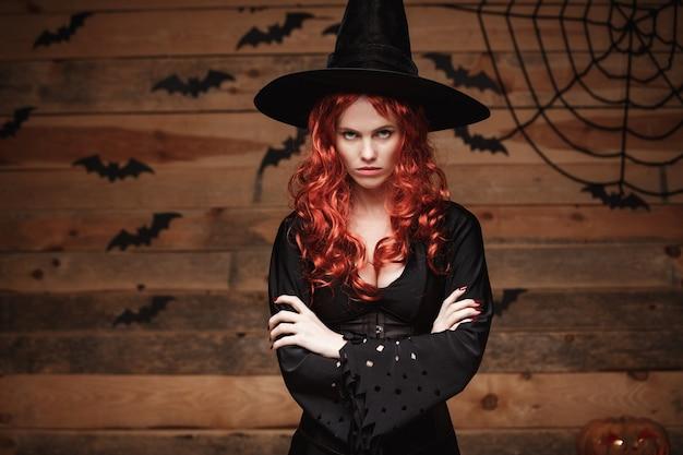 古い木製スタジオの背景に怒った顔でポーズをとって腕を保持しているハロウィーンの赤い髪の魔女