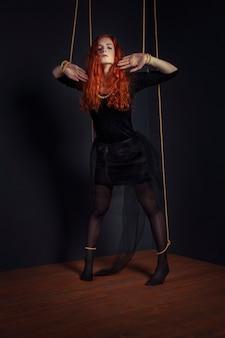 Halloween redhead woman marionette doll tied with ropes. girl doll tied with ropes with hands and feet