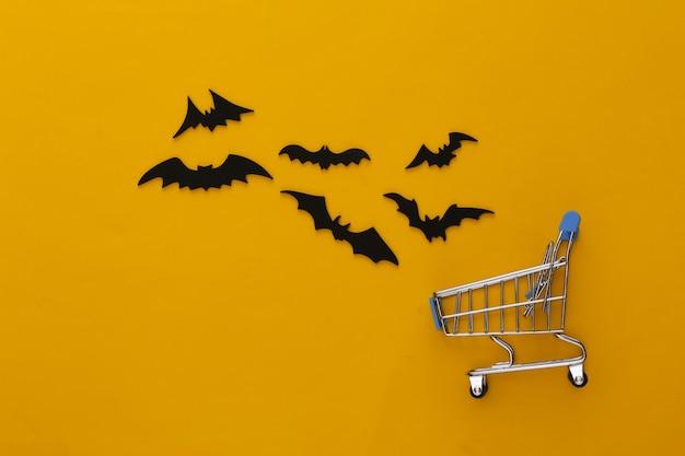 ハロウィンセール、ショッピング。スーパーマーケットのトロリーと青の空飛ぶコウモリ。ハロウィーンの装飾