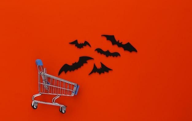 ハロウィンセール、ショッピング。オレンジ色のスーパーマーケットのトロリーと空飛ぶコウモリ。ハロウィーンの装飾
