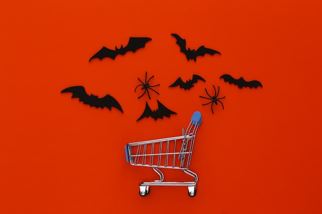 ハロウィンセール、ショッピング。スーパーマーケットのトロリーと空飛ぶコウモリ、オレンジ色のクモ。ハロウィーンの装飾