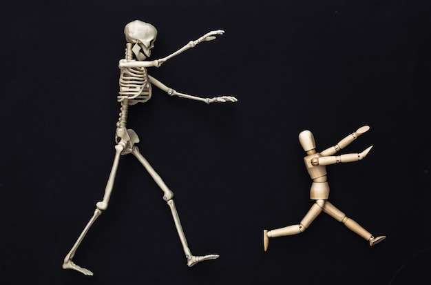 Halloween scary concept. wooden puppet runs away from the skeleton on a black