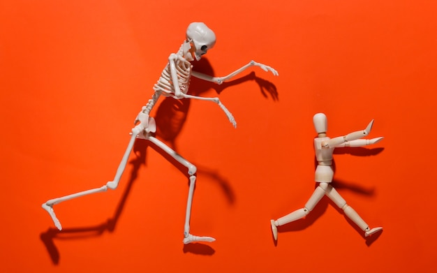 Halloween scary concept. wooden puppet runs away from the skeleton on orange bright