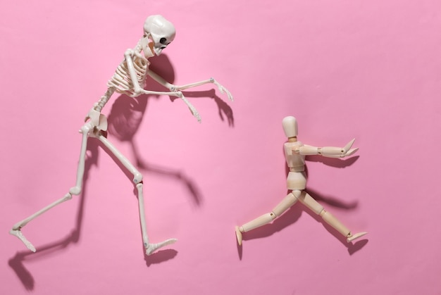 Halloween scary concept. wooden puppet runs away from the skeleton on pink bright
