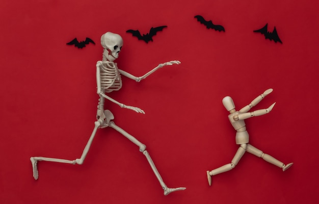 Halloween scary concept. wooden puppet runs away from the skeleton on red with flying bats