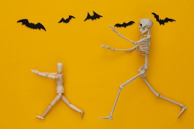 Halloween scary concept. wooden puppet runs away from the skeleton on yellow with flying bats