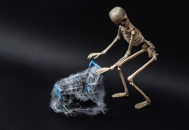 Хэллоуин, страшная тема. поддельный скелет и тележка для покупок в сети на черном.