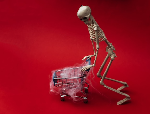 Хэллоуин, страшная тема. поддельный скелет и тележка для покупок в сети на красном.