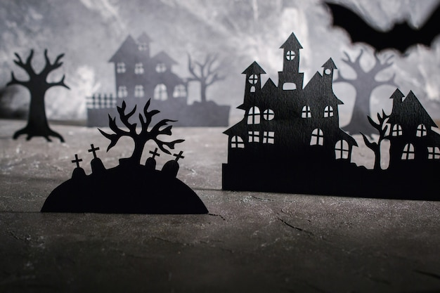 Halloween scene.  paper houses and dark misty trees in graveyard