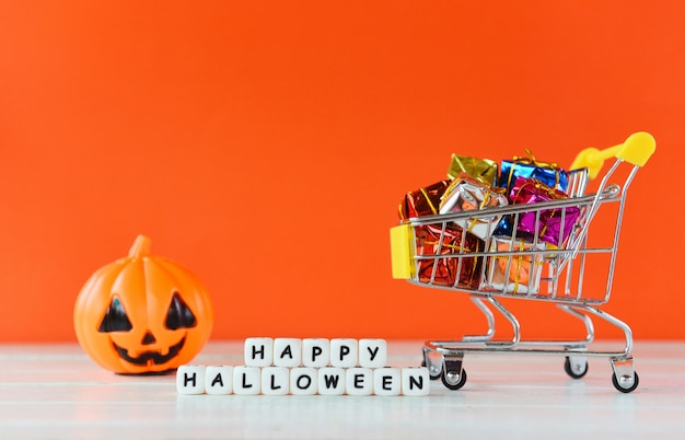 Halloween shopping holiday concept - word blocks happy halloween decorations and pumpkin jack o lantern with gift box in a shopping cart
