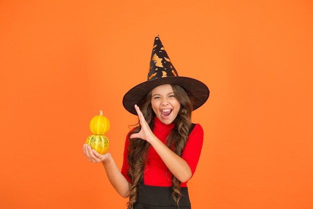 Halloween shouting child in witch hat costume making spell with pumpkin, halloween magic.