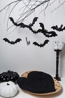 나뭇가지에 많은 검은 박쥐와 흰색 배경에 호박과 할로윈 실루엣