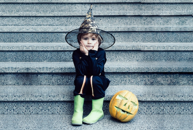 Хеллоуин скелет маленький ребенок развлекается на свежем воздухе на ступеньках имеет счастливого маленького мальчика на хэллоуинском п ...