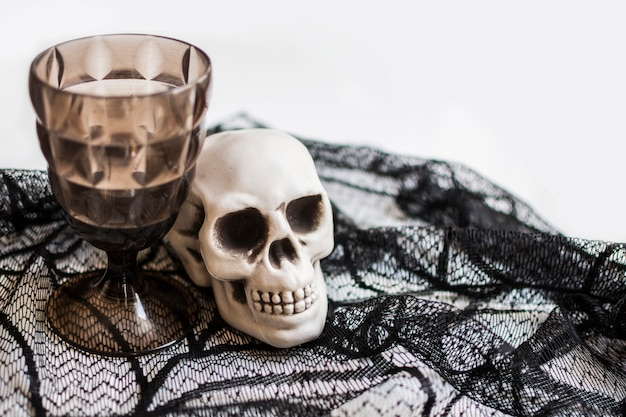 Halloween skull and a dark glass on a cobweb texture background