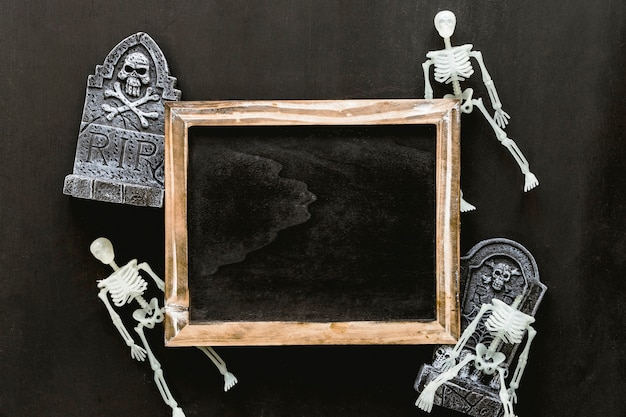 Halloween slate composition with skeletons and tombstones