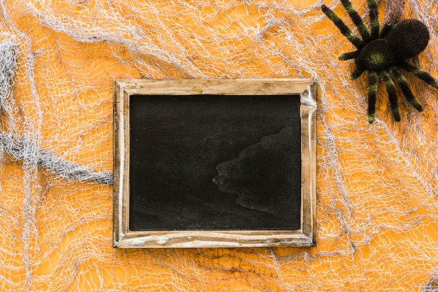 Halloween slate composition with spider on cobweb