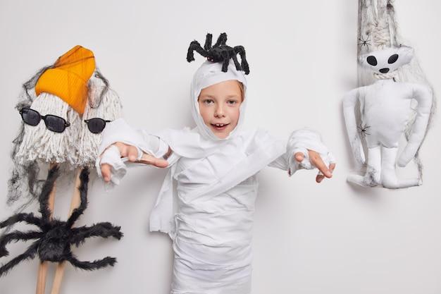 Хэллоуин. жуткое маленькое детское привидение делает трюк или угощает с пауком на голове, говорит, что я съем тебя, готов отпраздновать вечеринку позы на белом