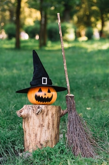 Halloween spooky pumpkin with hat on stump near broomstick