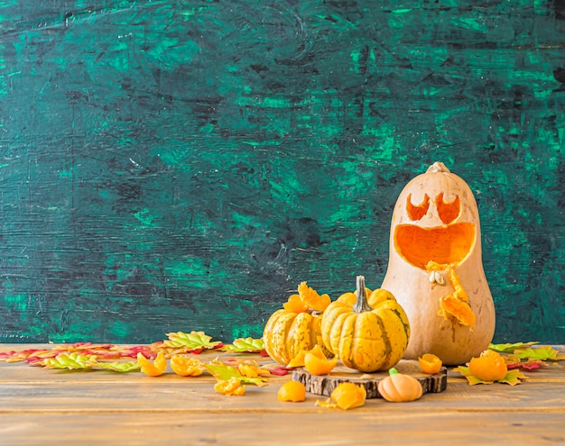 Halloween squash and 2 small pumpkins with funny face, front view, copyspace on green ,