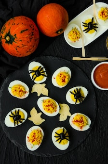 Halloween stuffed eggs with cheese and mustard on a black stone