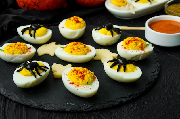 Halloween stuffed eggs with cheese and mustard on a black stone.