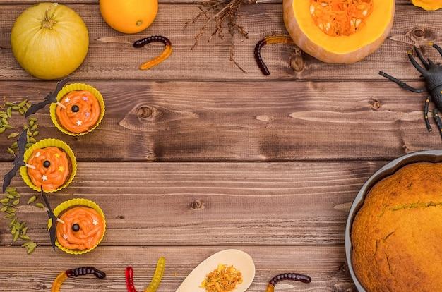 コピースペースのあるハロウィーンの表面:カボチャのパイとオレンジ色のカボチャのカップケーキ、甘いワーム、クモ