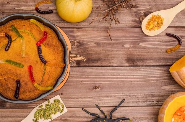 コピースペースを持つハロウィーンの表面:オレンジ色のカボチャとカボチャのパイ、甘いワーム、スパイダー、木製の表面