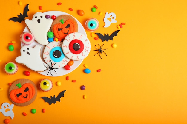 Halloween sweets on colored background close up top view with place for text