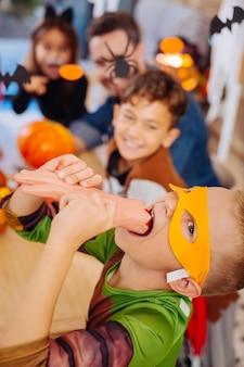 ハロウィンのお菓子。ハロウィーンの忍者タートルコスチュームを着て、明るく怖いお菓子を食べるトリックをしているかわいい男の子