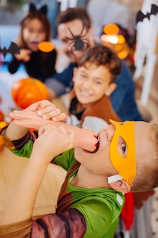 Halloween sweets. cute boy wearing ninja turtle costume for halloween playing tricks eating bright and scary sweets
