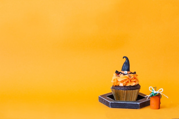 ハロウィーンのシンボル、休日の準備。オレンジ色のカボチャのカップケーキと木の装飾。