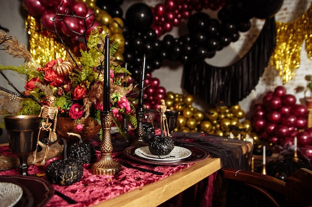 Halloween table decorated with some scary ornaments, such as a skull, a black bat