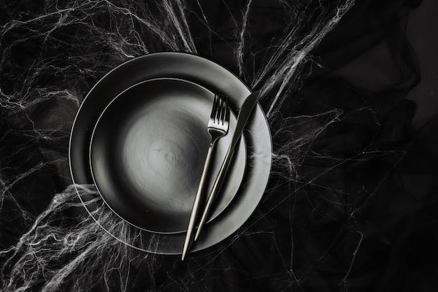 暗い背景のハロウィーンのテーブルの設定。蜘蛛の巣のある黒いテーブルの上の皿。フラットレイ、トップビューのトレンディな休日のコンセプト。