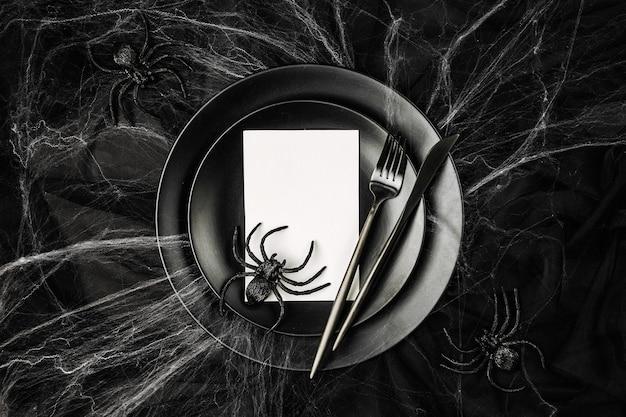 Сервировка стола хэллоуин на темном фоне. блюдо с пустой карточкой на черном столе с паутиной. плоская планировка, вид сверху модная концепция праздника.