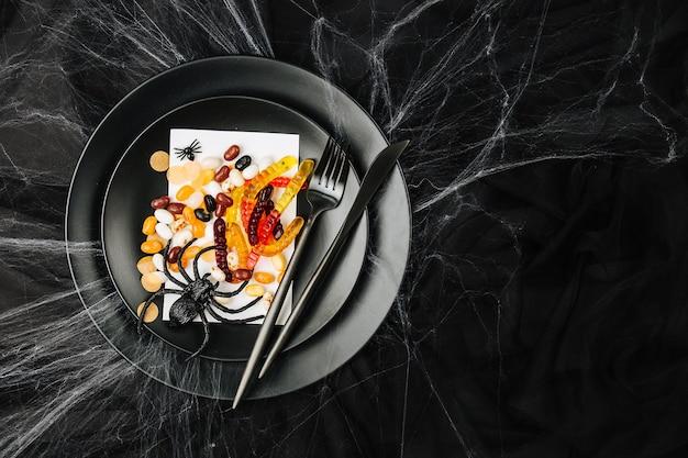 暗い背景のハロウィーンのテーブルの設定。蜘蛛の巣のある暗いテーブルの上でお菓子を使った料理。フラットレイ、トップビューのトレンディな休日のコンセプト。