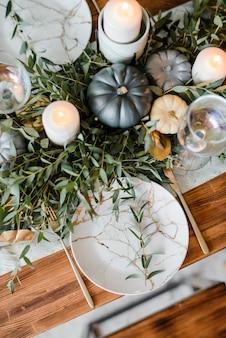 Сервировка стола хэллоуин на темном фоне. блюдо со сладостями на темном столе с черной и золотой тыквой. плоская планировка, вид сверху модная концепция праздника.