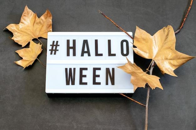 Текст хэллоуина с сухими ветвями деревьев и золотыми листьями. плоская планировка.