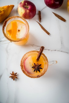 Хэллоуин, день благодарения. традиционные осенние, зимние напитки и коктейли. пряная горячая тыквенная сангрия, с яблоком, корицей, анисом. на белом мраморном столе, в стеклянных кружках. вид сверху копией пространства