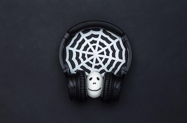 할로윈 테마입니다. 손으로 그린 무서운 유령 얼굴이 있는 달걀은 헤드폰과 검은색 배경의 웹에서 음악을 듣습니다.