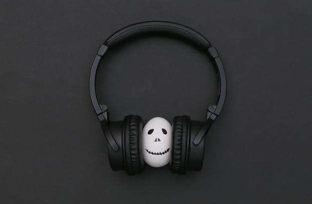 할로윈 테마입니다. 손으로 그린 무서운 유령 얼굴이 있는 달걀은 검은 배경에 헤드폰으로 음악을 듣습니다