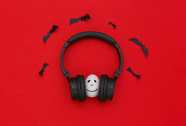 할로윈 테마입니다. 손으로 그린 무서운 유령 얼굴이 있는 달걀은 빨간색 배경에 헤드폰으로 음악을 듣습니다.