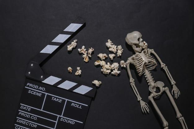 ハロウィーンのテーマ。黒の背景に映画の鳴子、ポップコーン、スケルトン。ホラー映画制作。上面図