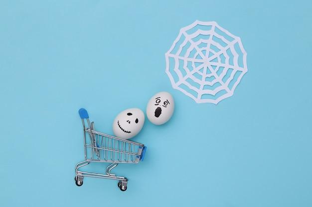 할로윈 테마입니다. 파란색 배경에 웹이 있는 손으로 그린 무서운 유령 얼굴이 있는 쇼핑 트롤리와 계란