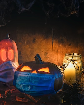 Halloween themed, spooky pumpkins wearing face masks and candles in a dark setting