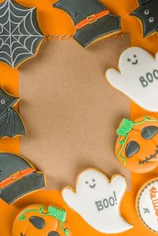 ハロウィーンは、砂糖漬けのジンジャーブレッドクッキーとキャンディー、トリックオアトリートコンセプトのトップビューコピースペース、トレンディな明るいオレンジ色の背景で背景を扱います