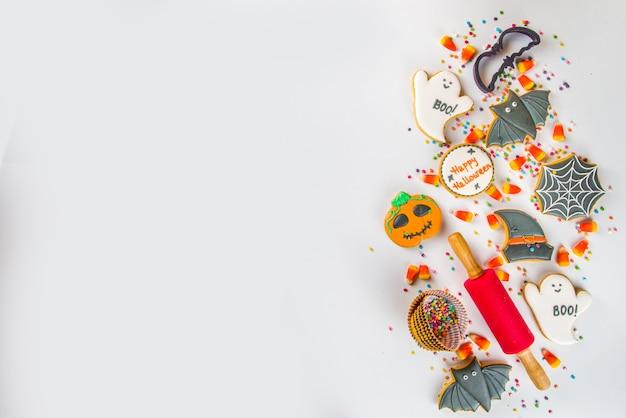 ハロウィーンは砂糖漬けのジンジャーブレッドクッキーとキャンディーで背景を扱います、トリックオアトリートコンセプトトップビューコピースペース白い背景コピースペース