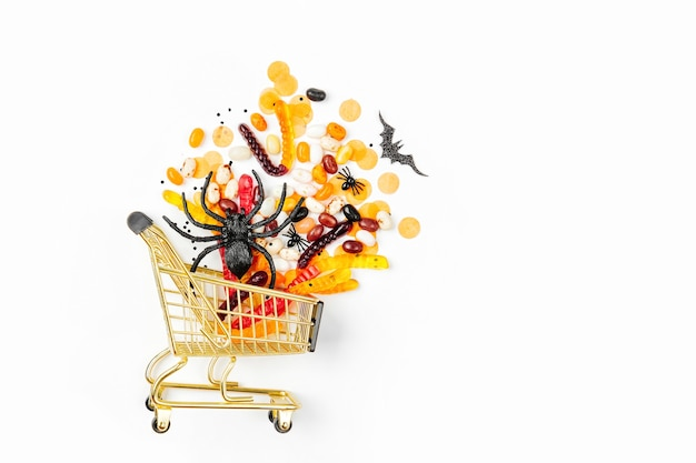 Halloween treats in a shopping cart on a white background. trick or treat, concept for halloween.   flat lay, top view